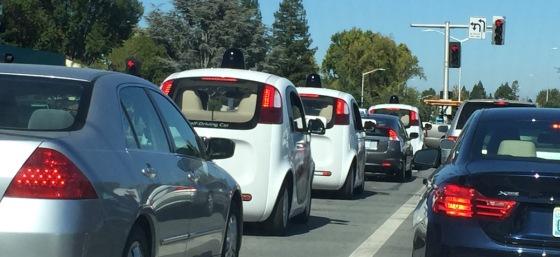 Three Google self-driving cars at the traffic light